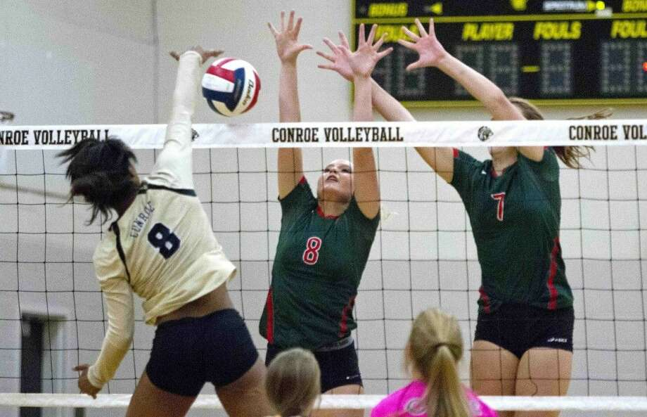 The Woodlands' Sophie Walls and Hannah Hickman go up to block a shot by Conroe's Kendra Butler during a volleyball game Tuesday. To view or purchase this photo and others like it, visit HCNpics.com.
