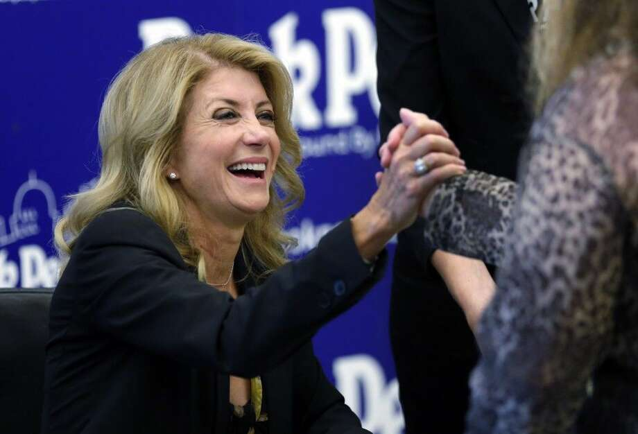 In this Sept. 11, 2014 photo, Texas Democratic gubernatorial candidate Wendy Davis visits with supporters at a book signing in Austin, Texas. Davis is running against Republican Texas Attorney General Greg Abbott in the general election.