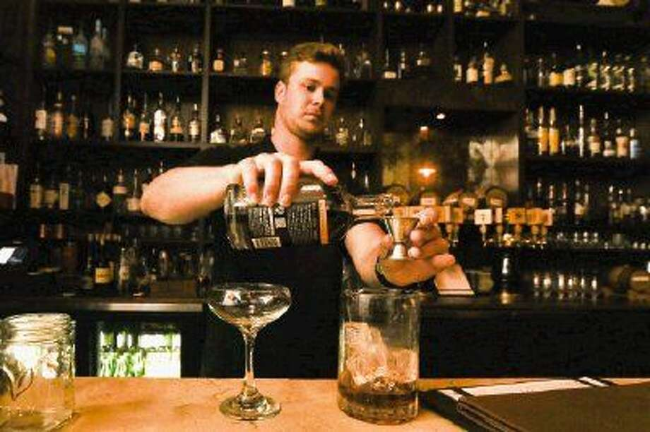 Bartender Walter Fowlkes creates a classic Manhattan cocktail at The Refuge Bar and Bistro. Photo: Michael Minasi
