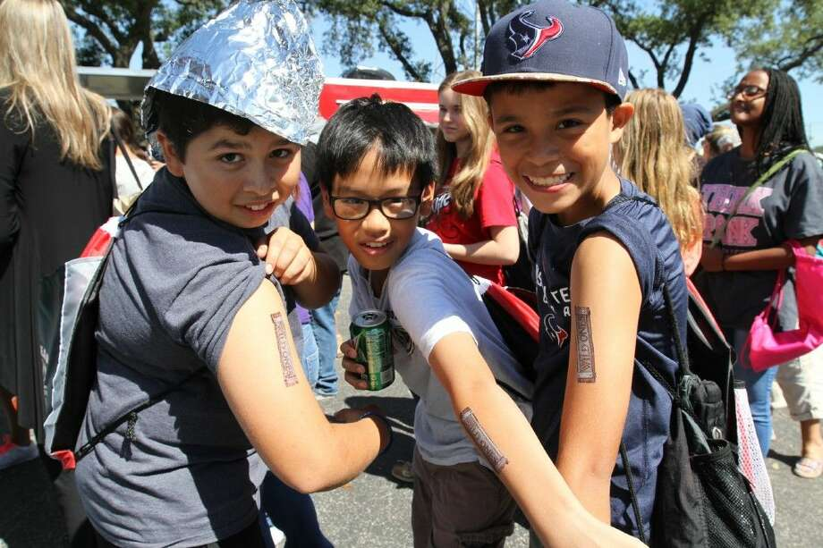 Beverly Hills intermediate seventh graders Jacob Acevedo, Dylan Ta and Tristan Pedraza show off their tattoos at the Tweens Read Festival.