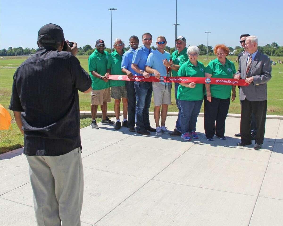 A photographer from the City of Pearland Communications Department rushes forward to take a picture of the ribbon-cutting ceremony.