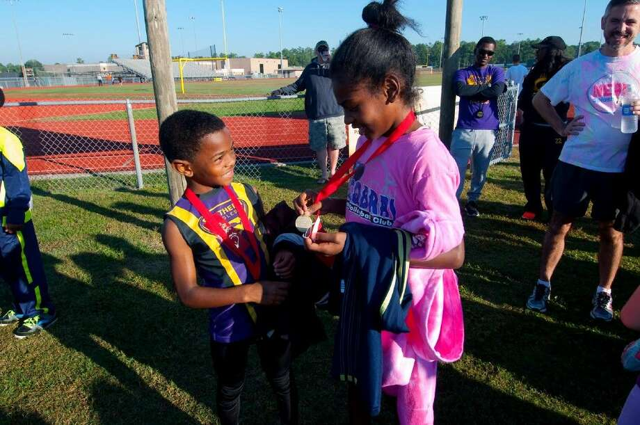 Eli Jacobs and Elyse Jacobs (brother and sister) admire their medals for winning first place in their races at the Red Ribbon Run Saturday, Oct. 25, at Klein Oak Stadium. Photo: Tony Gaines