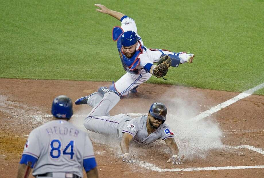 Texas Rangers' Delino DeShields, center, scores past Toronto Blue Jays catcher Russell Martin during the third inning of Game 1 of the American League Division Series in Toronto on Thursday.