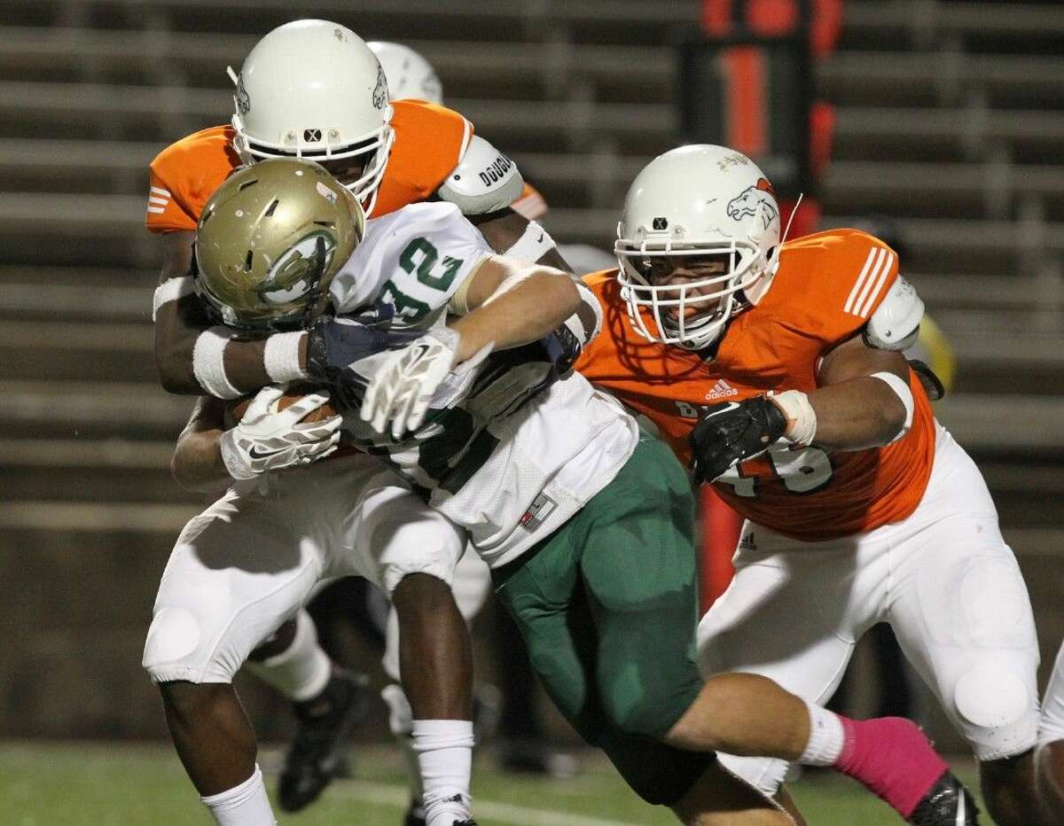 Bush's Matia Gardner and Qualyin Dorsey wrap up Santa Fe's Josh McKinney, Oct. 24 at Mercer Stadium in Sugar Land. To view or purchase this photo and others like it, go to HCNPics.com.