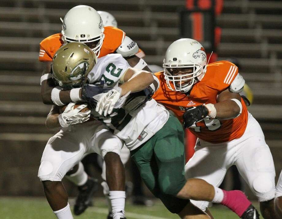 Bush's Matia Gardner and Qualyin Dorsey wrap up Santa Fe's Josh McKinney, Oct. 24 at Mercer Stadium in Sugar Land. To view or purchase this photo and others like it, go to HCNPics.com. Photo: Alan Warren