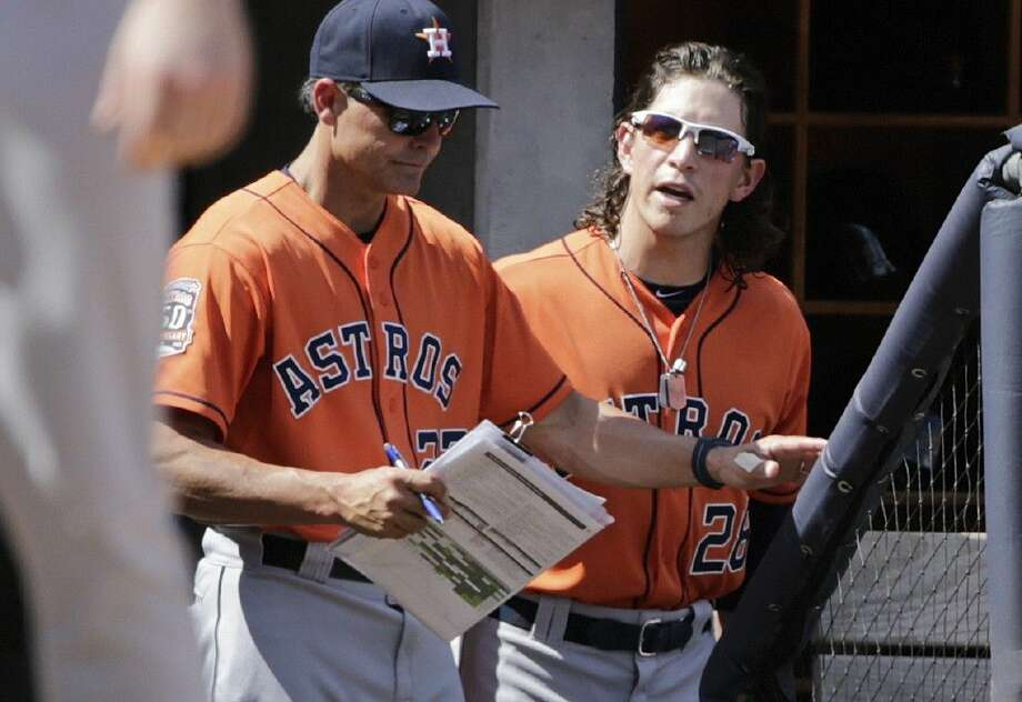 Houston Astros' Colby Rasmus, right, yells at the home plate umpire after being ejected from the game as bench coach Trey Hillman, left, blocks his path during the fifth inning against the New York Yankees Wednesday in New York.