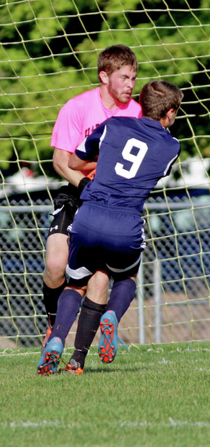 Harbor Beach goalie Mitchel Smith holds on to the ball after USA's Kye Jacoby (9) collided with him.