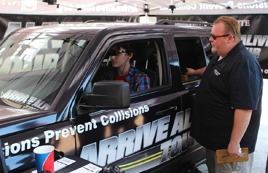 Unite Team Leader Patrick Sheehy, right, shows student Dustin Graves, of Pearland, how difficult it is to operate a car after drinking alcohol during the Dolphin Wing Fling on October 7.