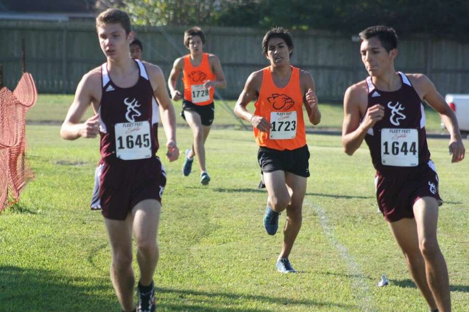 William Wagner (left) and Alec Trevino make the turn at the intersection of X and Georgia Street as they enjoy a view among the Top-10 during the 21-6A boys race. They'll be at Atascocita High Saturday. Photo: Robert Avery