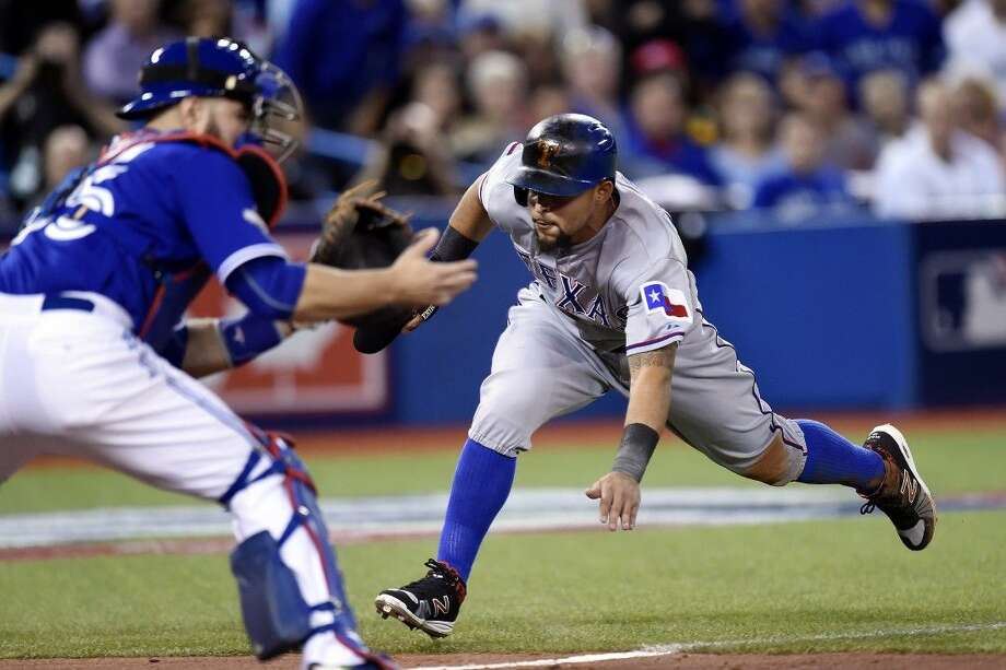 Texas Rangers' Rougned Odor slides safely home on a sacrifice fly during the second inning in Game 2 of the American League Division Series in Toronto on Friday.