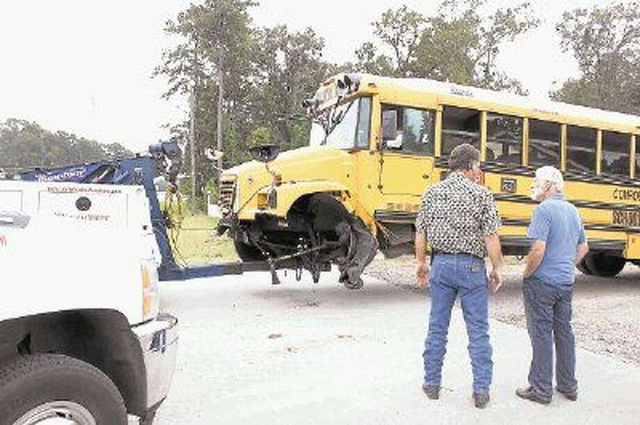 Witnesses stand near a wrecked Conroe ISD school bus on FM 1314. The crash sent two students to the hospital.