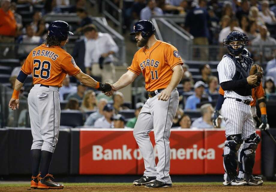 Houston Astros' Colby Rasmus (28) greets Evan Gattis (11) at the plate after scoring on Gattis's fifth-inning, two-run home run in a baseball game against the New York Yankees at Yankee Stadium in New York, Tuesday.