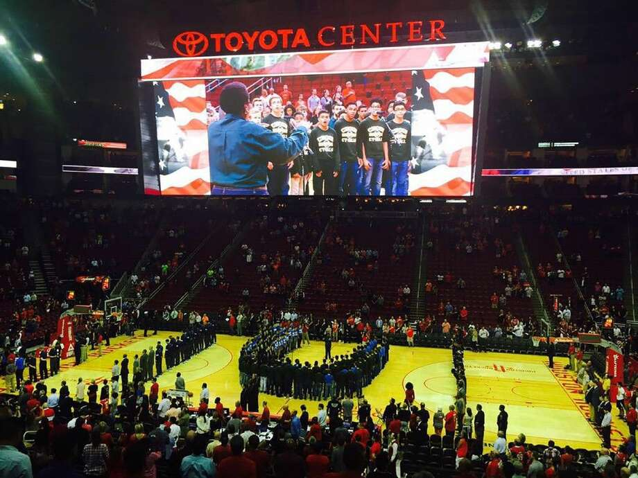 Cypress Falls choir director Deidre Douglas directs men's choir members from Cypress Falls, Truitt and Labay, who are visible on the large scoreboard at the Toyota Center.