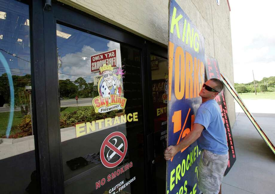 Andrew Esser boards up the glass doors at the entrance of Sky King Fireworks in preparation for Hurricane Matthew, Wednesday, Oct. 5, 2016, in Cocoa, Fla. (AP Photo/John Raoux) Photo: John Raoux, STF / Copyright 2016 The Associated Press. All rights reserved.