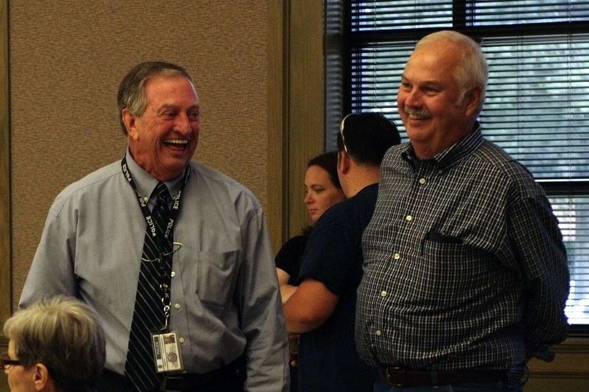 Former Liberty City Council member and current Pct. 1 County Commissioner Mike McCarty (at right) shares a laugh with Liberty Police Chief Billy Tidwell at the chief's farewell reception Wednesday, Oct. 29.