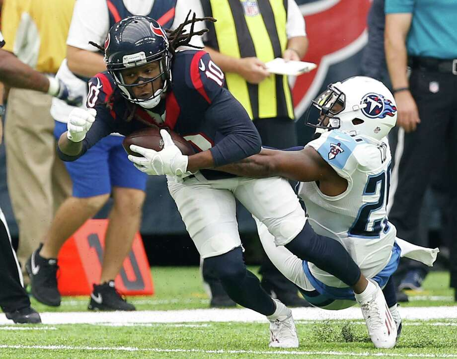 Houston Texans wide receiver DeAndre Hopkins (10) stretches for a first down as he is hit by Tennessee Titans cornerback Perrish Cox (20) during the fourth quarter of an NFL football game at NRG Stadium on Sunday, Oct. 2, 2016, in Houston. Photo: Brett Coomer /Houston Chronicle / © 2016 Houston Chronicle