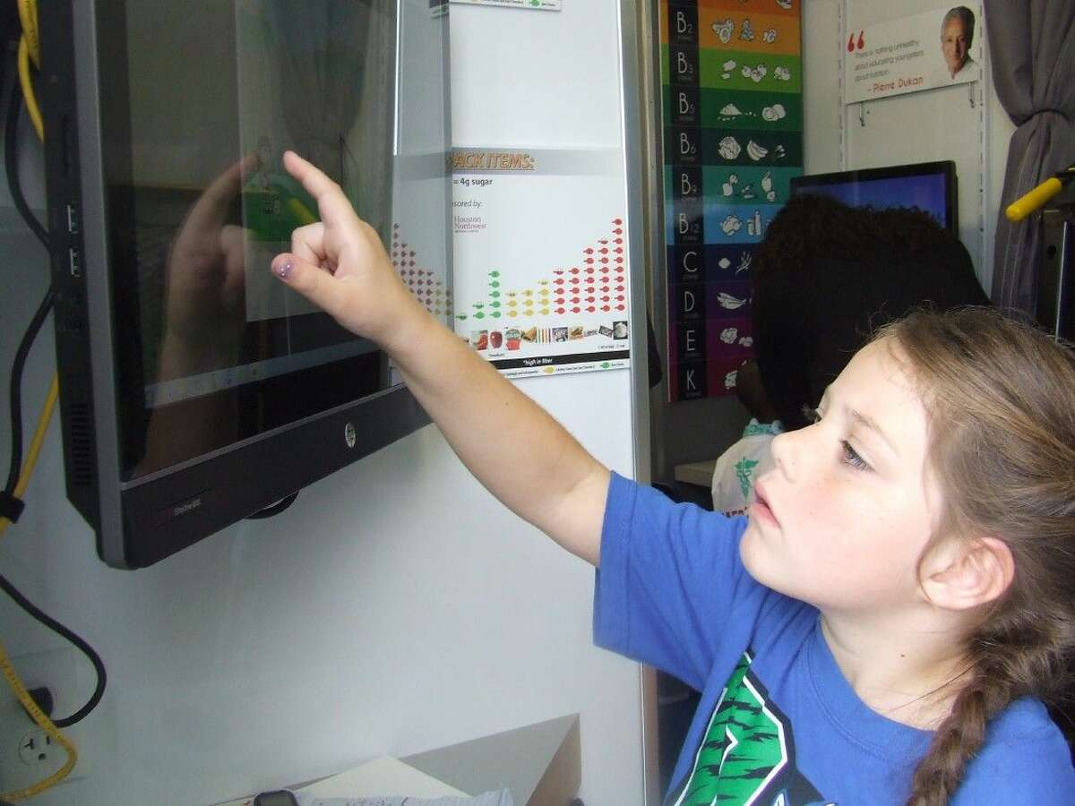 Bailey DePhilippis, a first-grader at Bernshausen Elementary School, plays a game in the S.T.E.A.M. Express trailer on Wednesday, October 29, 2014.