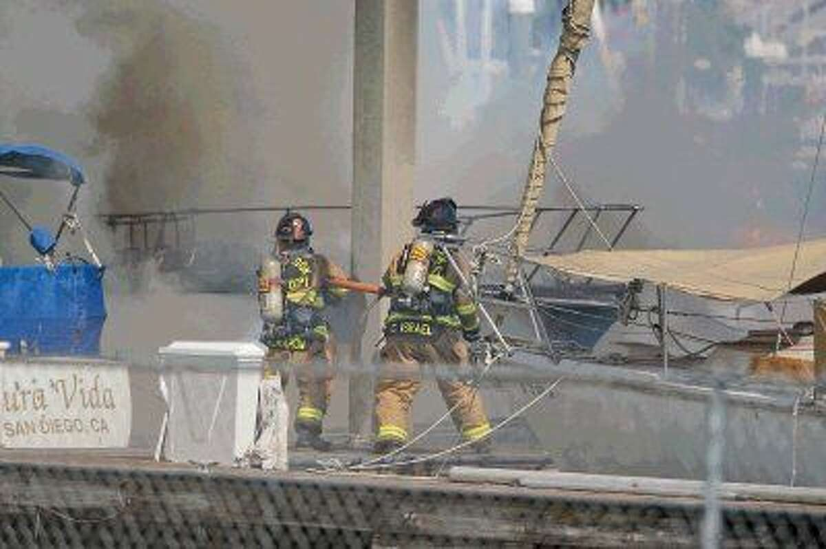 Firefighters work on the dock to contain the boat fires in Kemah.