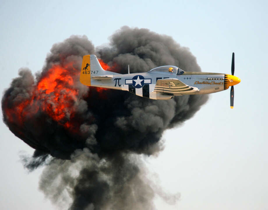 A P-51 flies past an explosion during a demonstration during Saturday's Wings Over Houston Airshow. Photo: Kar B Hlava