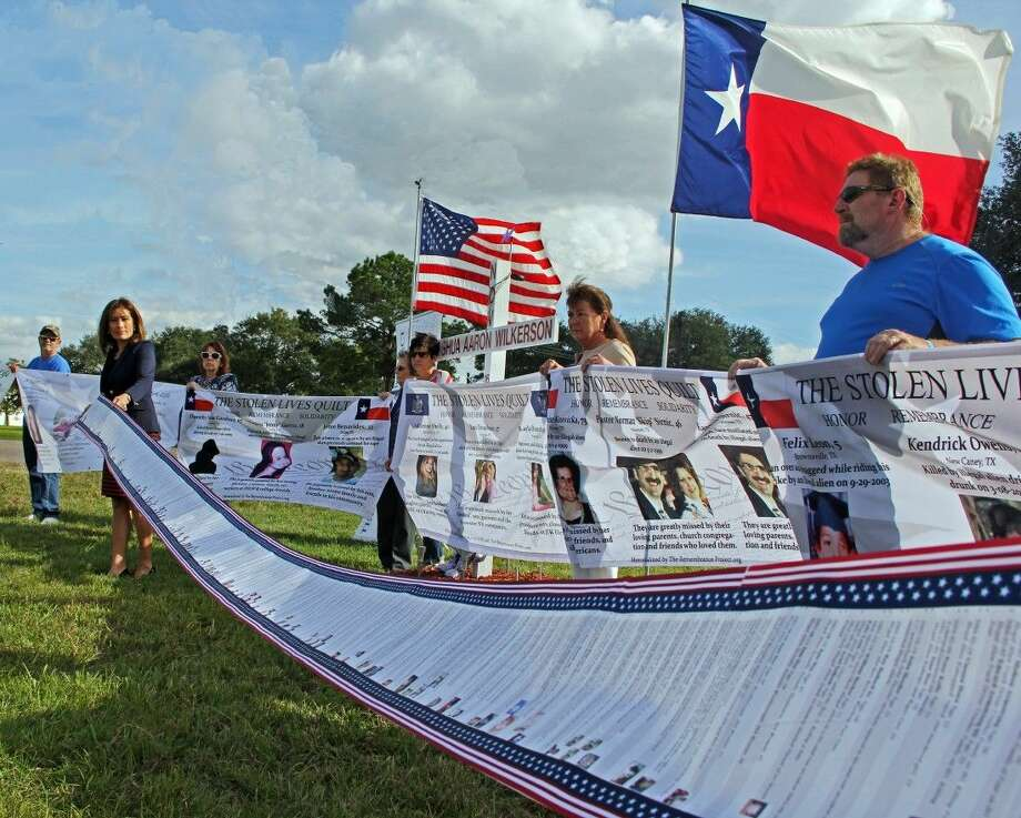 Activist Maria Espinoza, Co-Founder and National Director for the Remembrance Project displays a 15 foot-long containing the names of murder victims killed by illegal immigrants. Behind her supporters hold quilts created to honor victims at a gathering held to mark the Fourth Annual National Day of Remembrance Sunday (Nov. 2). Photo: Kristi Nix