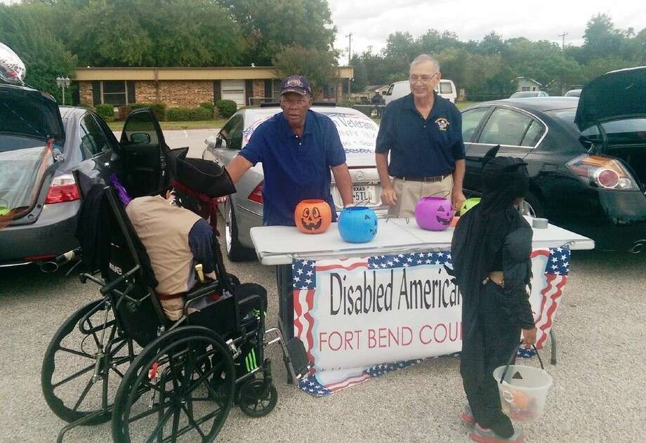 """CHEERED, NOT """"SKEERED"""" - Aging American military veterans residing at Sugar Land Health Care Center are greeted and treated on Halloween in the nursing home's parking lot by members of Disabled American Veterans Chapter 233 of Fort Bend County. Edgar Spears and Carlos Lopez present candy to a wheelchair-bound veteran who resides there. Photo: Submitted"""