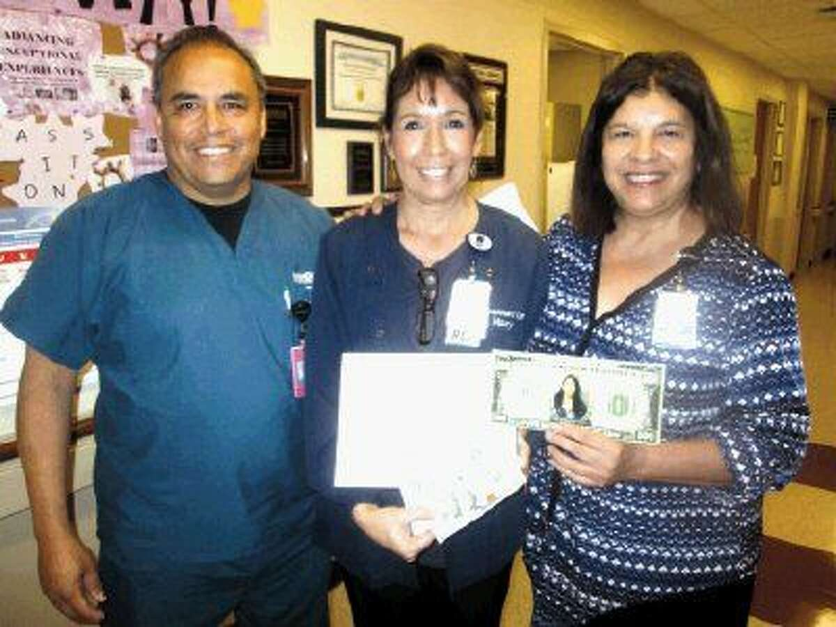 Mary Fruzia (center) received an award and a cash award as Memorial Hermann Respiratory Therapist of the Year from Robert Menchaca of Memorial Hermann Southwest Hospital and organizer of the award, and Suzanne Croft, director of Cardiopulmonary Services at Memorial Hermann Northeast.
