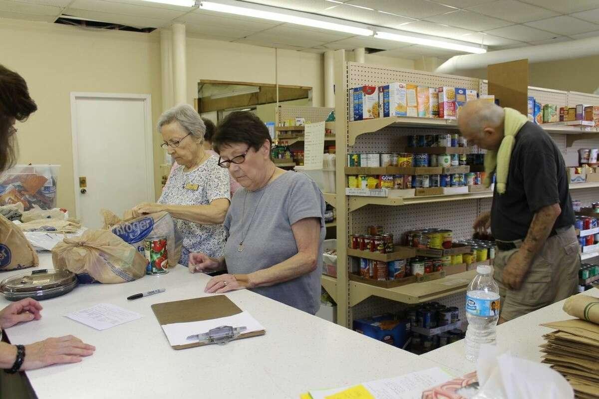 TEAM Volunteers package food bags for families.
