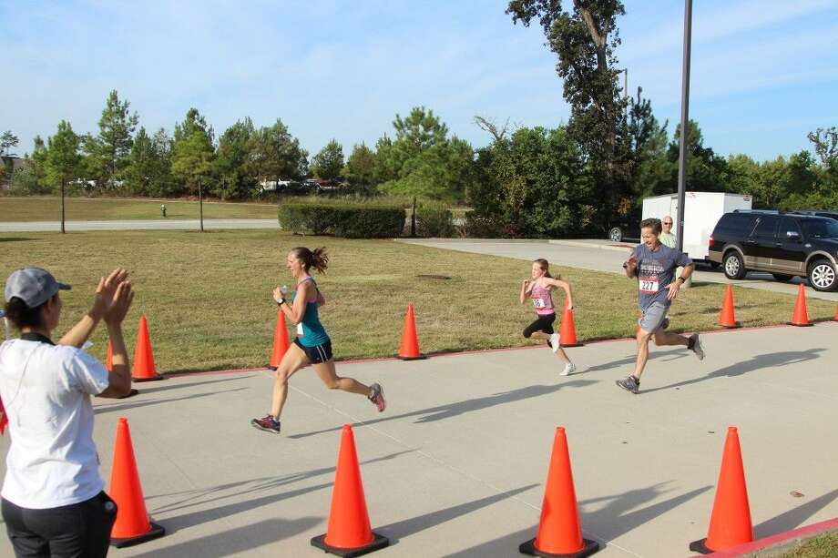 Attendees cheer on participants in the Team Never Quit Run to Remember 4-miler at Creekside YMCA in The Woodlands..