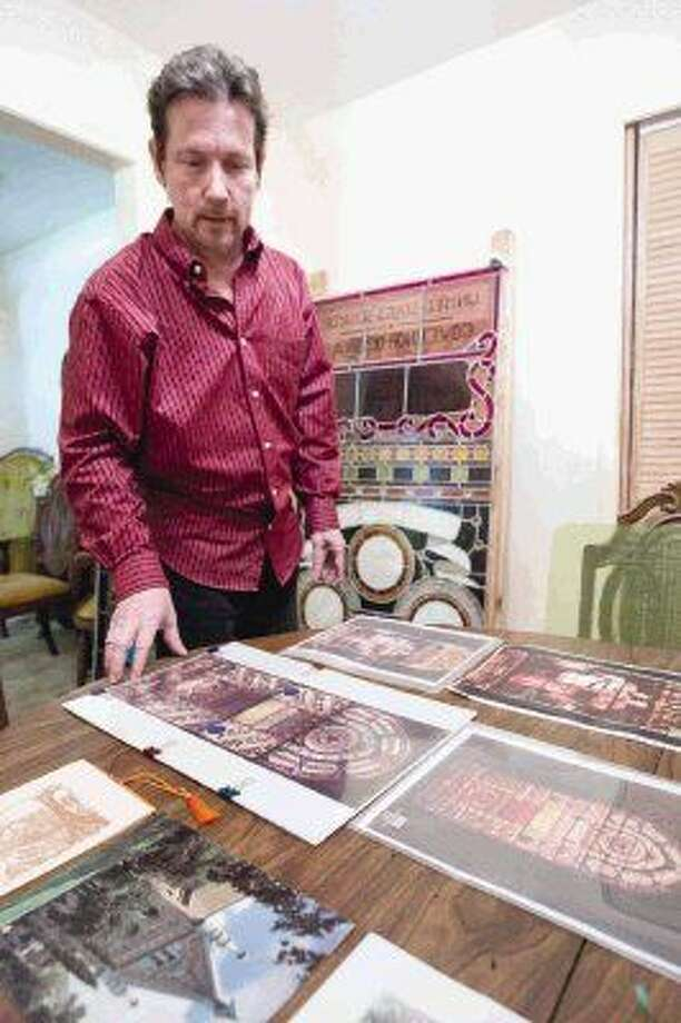 Sam Houston State University alumnus Joe Janczak shows old images of the 17-foot stained glass window he rebuilt honoring Sam Houston and Texas heroes at his home in Spring. Photo: Jason Fochtman