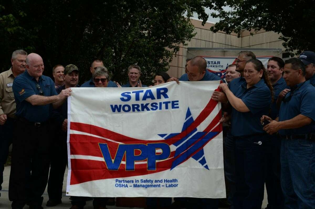 Members of the VPP team hold a banner presented by OSHA on Thursday morning.
