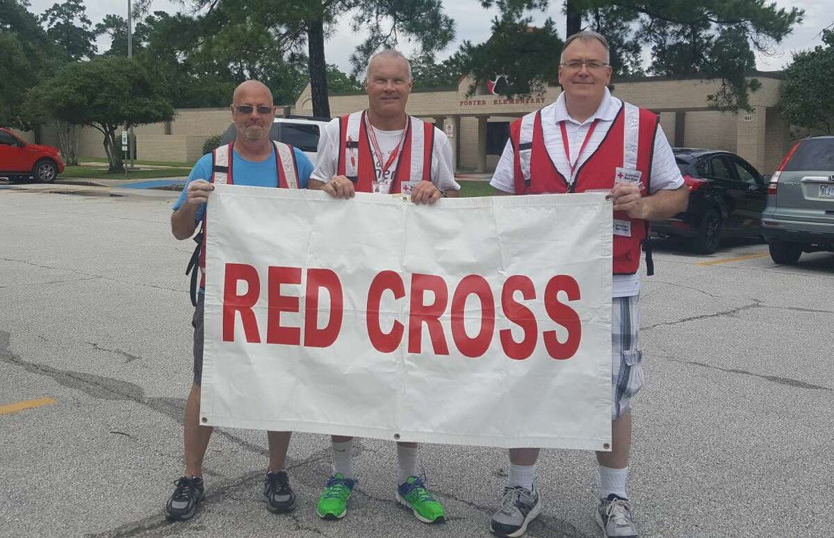 Red Cross volunteers Sam Glick (left,) Tay Omana (center,) and Frank Hall (right) pose at Foster Elementary School where they set up a temporary distribution center with flood relief supplies Friday, June 3.