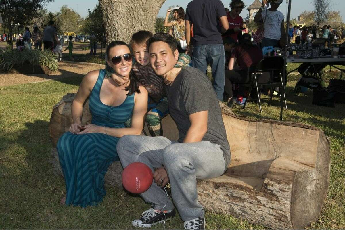 Contractors for Riverstone's newly opened Big Adventure Park crafted downed trees into usable benches and stools for the nature-themed playground. Shown here during the Trail of Treats park grand opening are Riverstone residents Michele and Jeremy Gutierrez and their son Dylan.