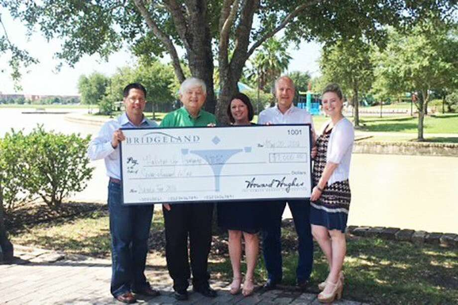 Executives from Bridgeland and The Woodlands Development Company present Habitat for Humanity Northwest Harris County (NWHC) with a 7,000 donation from proceeds from Nature Fest. From left to right are Heath Melton, Vice President of Master Planned Communities, Residential Development for The Woodlands Development Company; Chad Greer, Director of Development for Habitat for Humanity NWHC; Lona Shipp, Marketing Manager for Bridgeland; Peter Houghton, Vice President of Master Planned Communities for Bridgeland; and Audrey Seykora, Digital Marketing Manager for The Woodlands Development Company. Photo: Submitted Photo