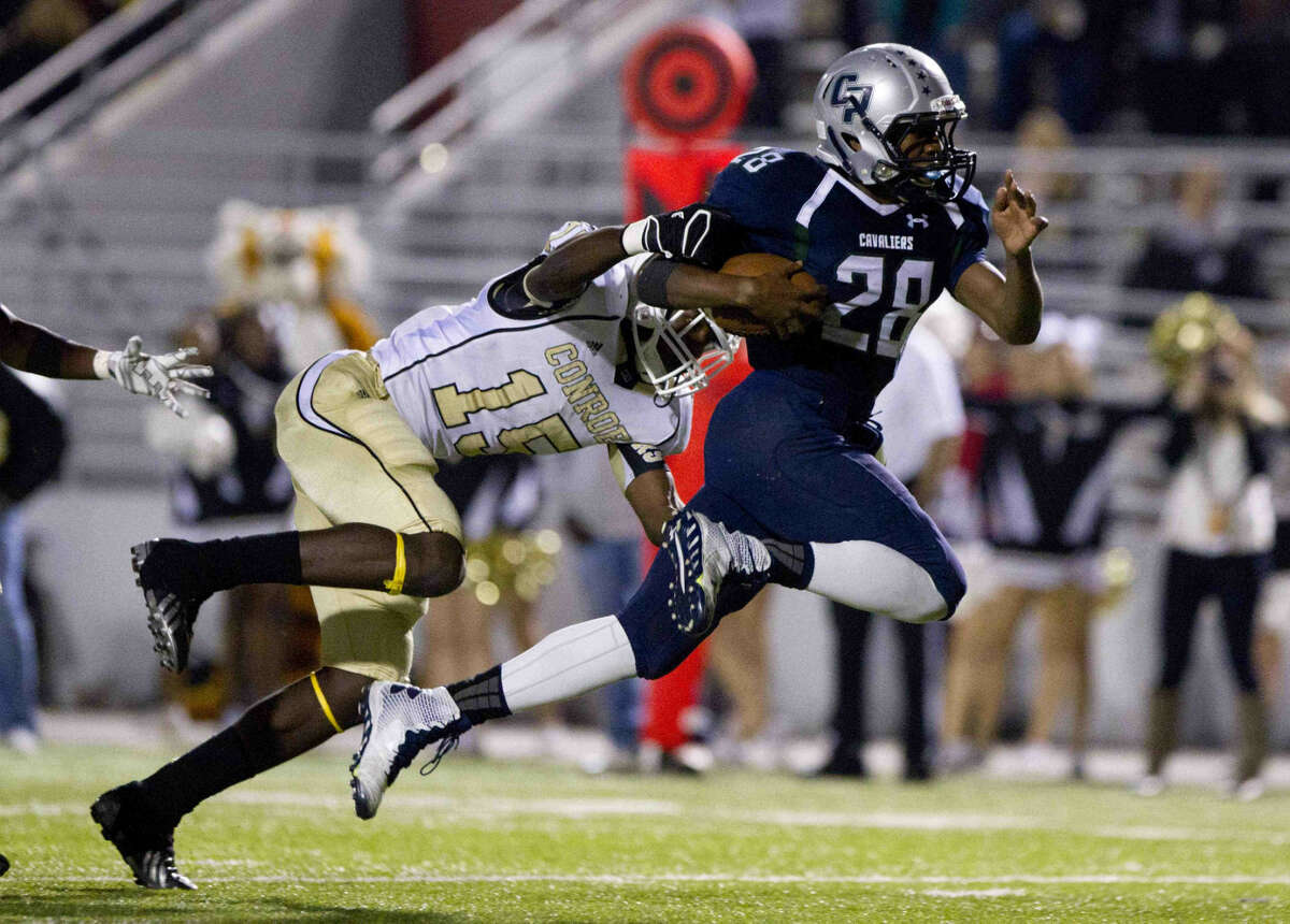 College Park running back A.J. Sanders leaps for extra yards as Conroe's Tradarian Jefferson defends during an high school football game Friday.