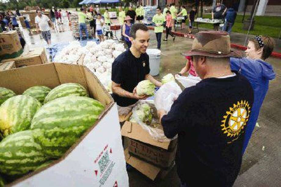 Bill Friebel, left, Jose Garcia, center, both of Rotary Club of The Woodlands, and volunteer Tori Wilson bag heads of lettuce during the Shenandoah Food Fair on Saturday at Woodforest Bank Stadium.