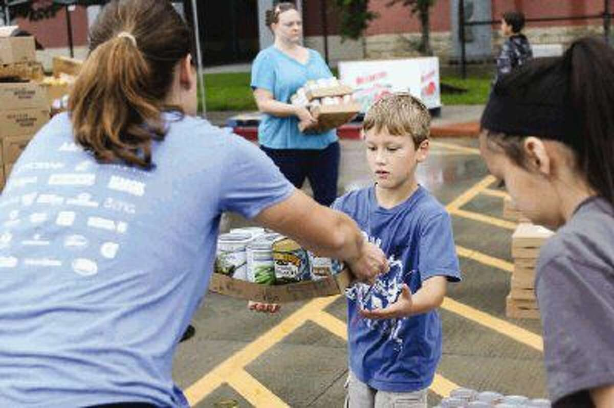 Brianne Crockett, of Rotary Club of The Woodlands, left, gives her son Braden Walker, 8, a carton of canned foods during the Shenandoah Food Fair on Saturday at Woodforest Bank Stadium.