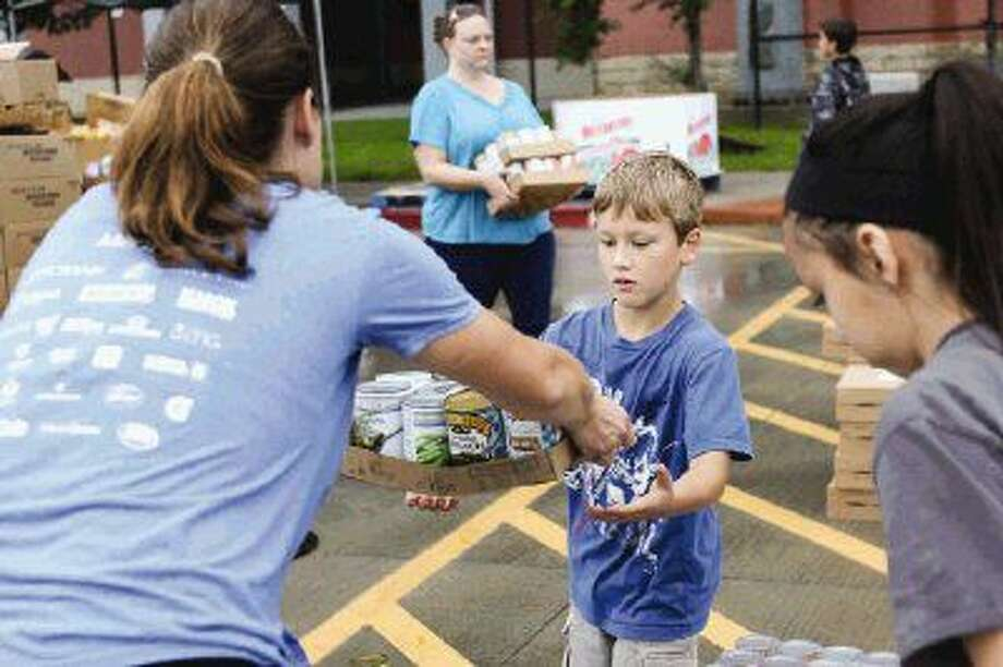 Brianne Crockett, of Rotary Club of The Woodlands, left, gives her son Braden Walker, 8, a carton of canned foods during the Shenandoah Food Fair on Saturday at Woodforest Bank Stadium. Photo: Michael Minasi