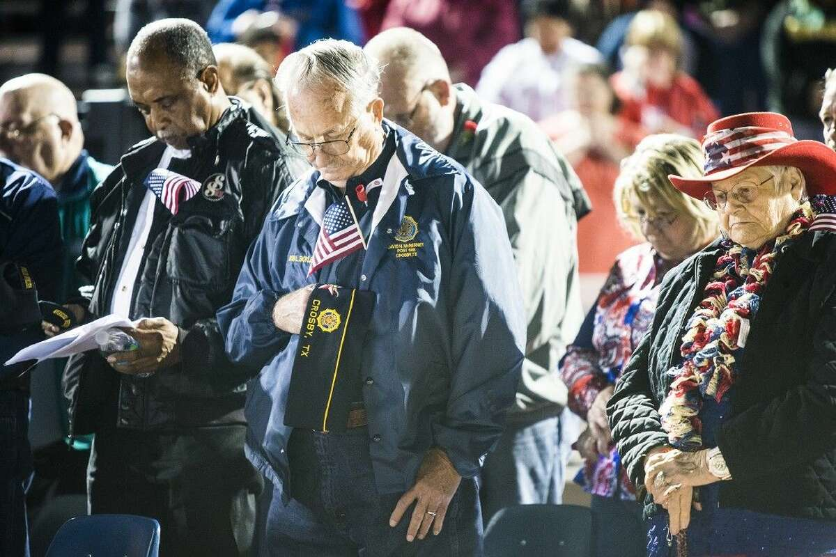 David McHerney, center, stands in silence for fallen soldiers during the Eastside Veteran's Celebration on Nov. 6, 2014, at Crosby High School.