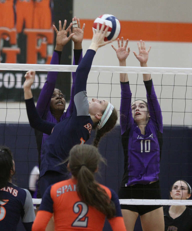 Seven Lakes' Camille Conner tips the ball against Jersey Village's Deyonna Evans and Lacie Aden during the 6A Area Volleyball Playoffs at Seven Lakes High School in Katy, Texas on Friday, November 7, 2014. Photo: Staff Photo By Alan Warren