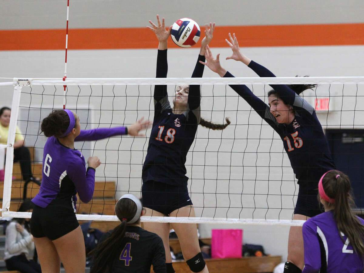 Jersey Village's Brandi Reed spikes against Seven Lakes' Camille Conner and Maggie O'Connell during the 6A Area Volleyball Playoffs at Seven Lakes High School in Katy, Texas on Friday, November 7, 2014.