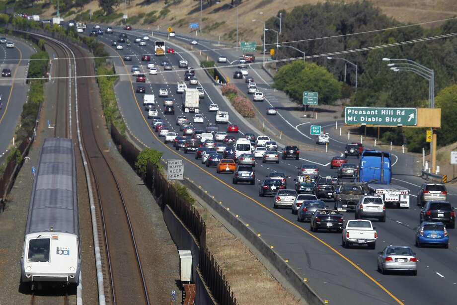 A BART train headed eastbound zips past commuters slowing to a crawl on westbound Highway 24 in Walnut Creek, Calif. on Thursday, June 25, 2015. Transportation is among the top concerns of Bay Area residents, according to a recent poll conducted by the Bay Area Council. Photo: Paul Chinn, The Chronicle