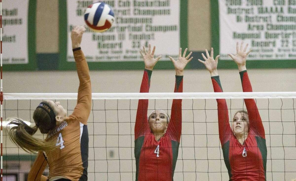 The Woodlands' Kendall Cook (4) and Rachel Reed go up to block a shot by Round Rock Westwood's Courtney Markes during a Region II-6A quarterfinal match on Tuesday at Brenham High School. To view or purchase this photo and others like it, visit HCNpics.com.