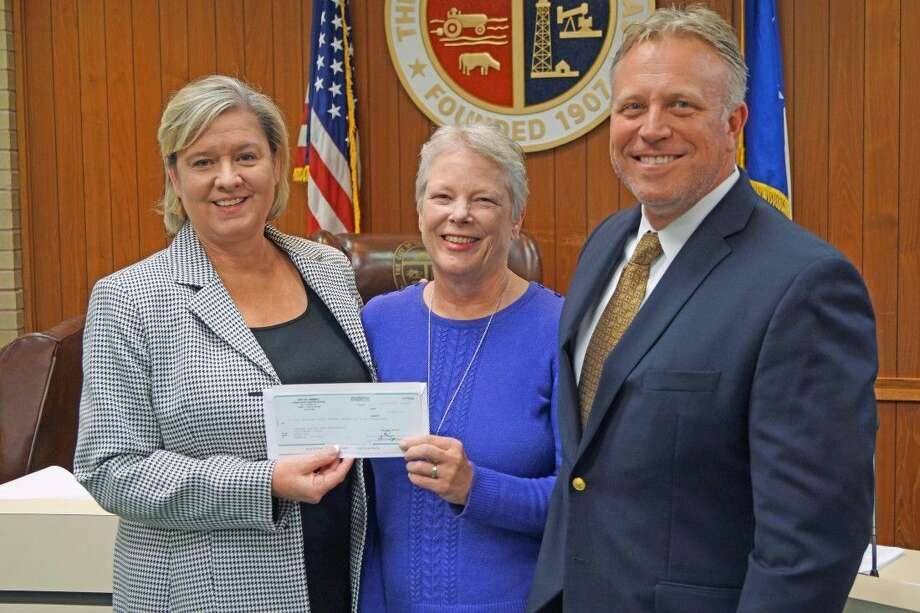 TOMAGWA executive director Judy Deyo receives a check for 10,836 from Tomball Mayor Gretchen Fagan and Assistant City Manager Rob Hauck during a recent meeting of the Tomball City Council. Photo: Submitted