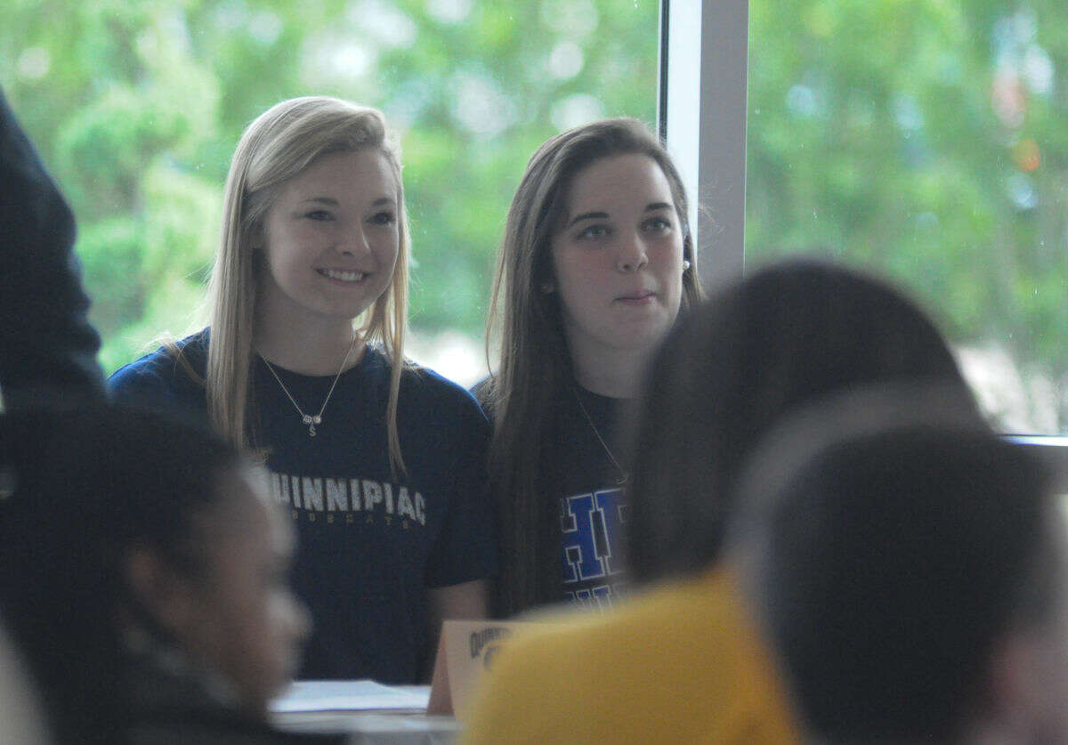 Kingwood student-athletes Sydney Dennis and Charlotte Hodges pose for a picture before signing their national letters of intent at a fall national signing day ceremony for Humble ISD at the Humble Civic Center on Wednesday.