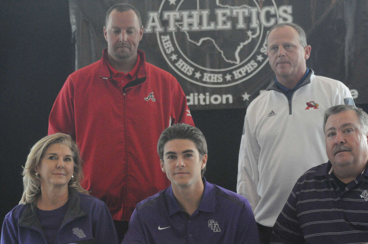 Atascocita baseball player Mitchell Johnson signs his national letter of intent to Stephen F. Austin at a fall national signing day ceremony for Humble ISD at the Humble Civic Center on Tuesday.
