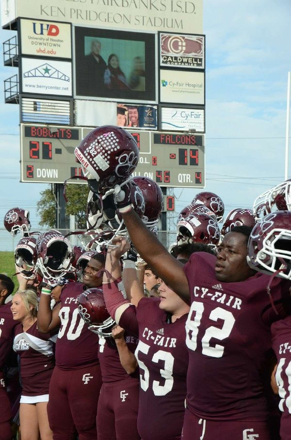Cy-Fair High School football players victoriously sing the school song after claiming a Region III-6A Division 1 playoff seed with a 27-14 win over Jersey Village High School on Saturday at Pridgeon Stadium.
