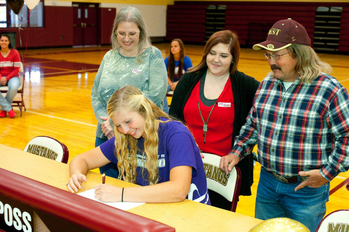 Magnolia West senior Reagan Trent surrounded by family signs a National Letter of Intent to play softball at Concordia University. Photo By Tony Gaines.
