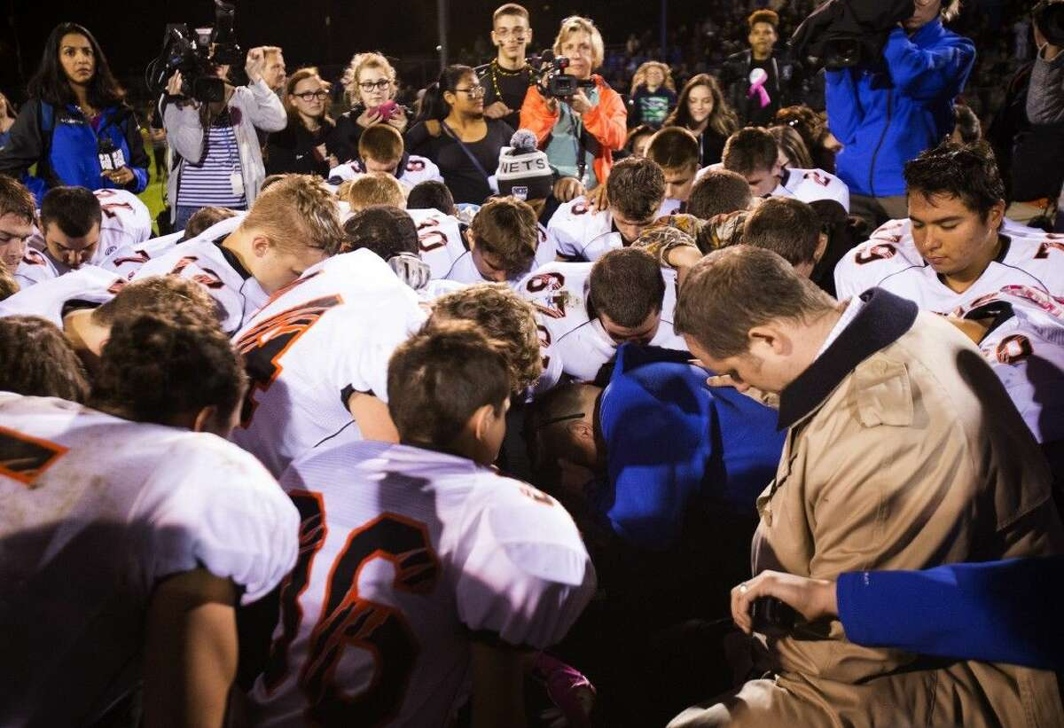 Bremerton High assistant footbal coach Joe Kennedy, center in blue, kneels and prays after his team lost to Centralia in Bremerton, Wash.