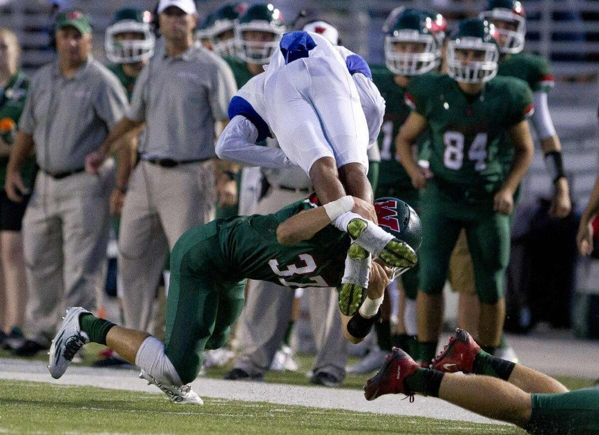The Woodlands linebacker Cole Sichley tackles Dekaney quarterback Adrian Hardy in midair during a high school football game Thursday. To view or purchase this photo and others like it, visit HCNpics.com.