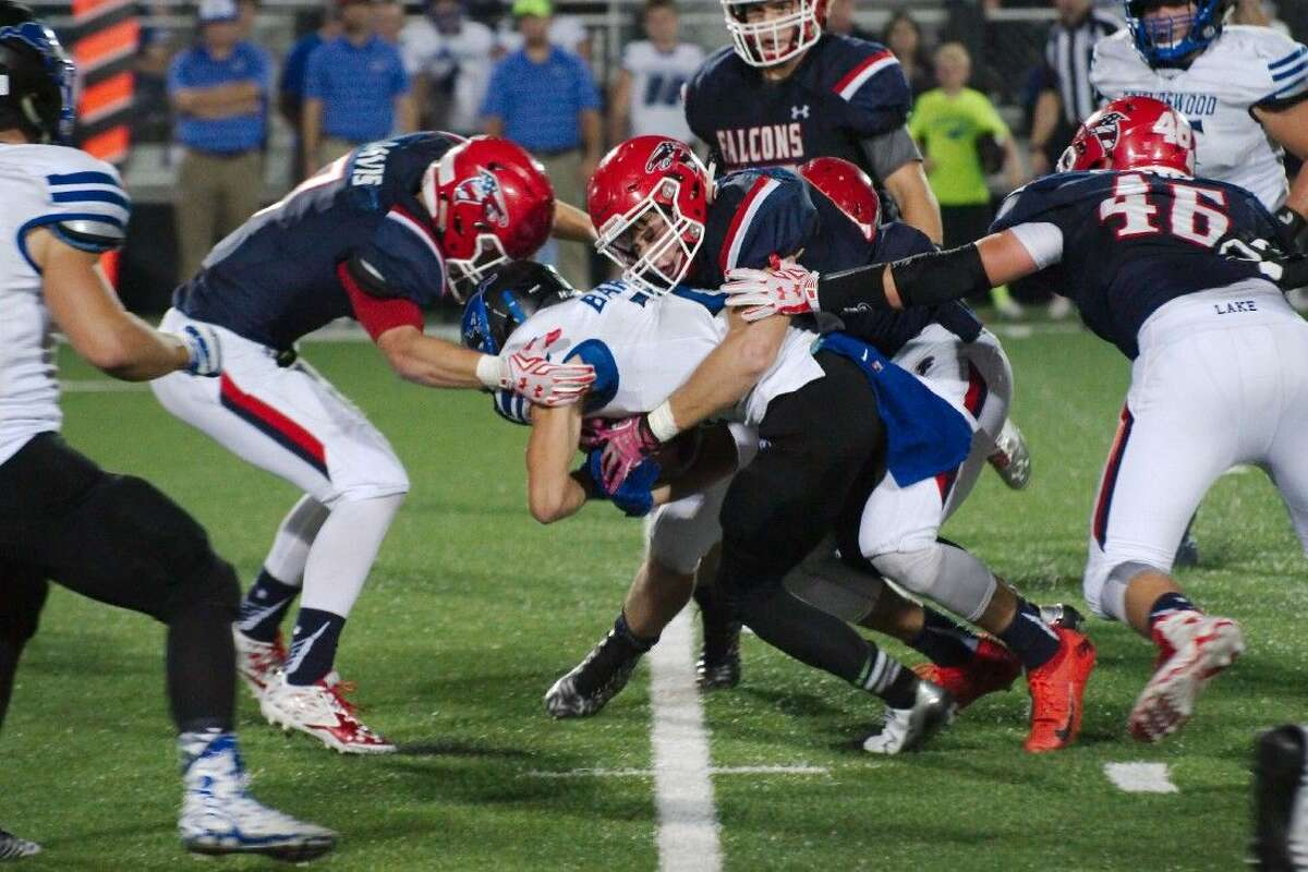 Friendswood running back Mason Barnes (21) is wrestled down by Clear Lake's Collin Davis (7) and Casen Bury (85) Thursday night.